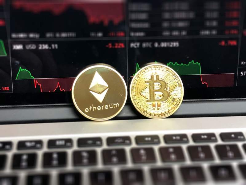 Bitcoin and Ethereum coins sitting on a computer