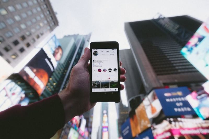 Man holding a phone and search for Dapps in the city
